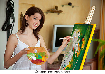 Young girl painting on an easel - Young woman is painting in...