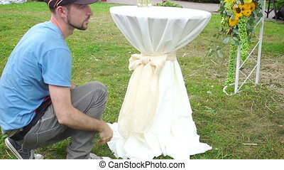 Florist man at work tying a bow on white wedding table....