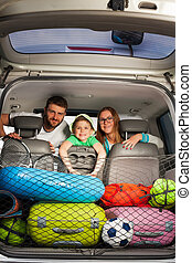 Happy family sitting in a minivan full of luggage - Happy...