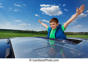 Smiling kid boy enjoying freedom on sunroof of car -...