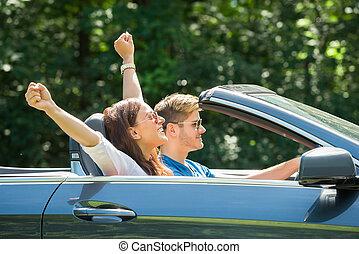 Couple Enjoying Drive In A Car - Happy Young Couple Enjoying...