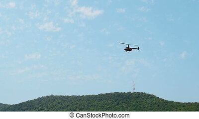 Black Helicopter Hovers And Flies In Air Against Blue Ssky...