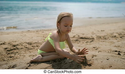 Adorable little girl playing on white sand beach