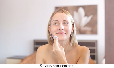 Young attractive woman cleaning her face.