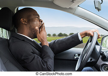 Businessman Yawning While Driving Car - Side View Of A Young...
