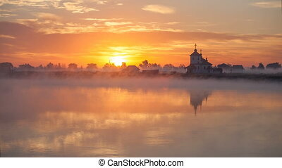 sunrise on the river near the church. Ukraine