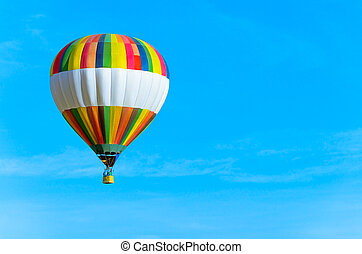 Colorful hot air balloon with blue sky and text space