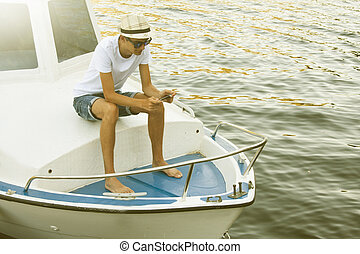 young man in the boat with mobile