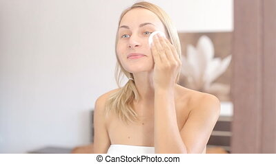 Young attractive woman cleaning her face