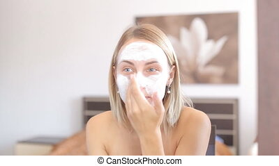 Female beauty, happy mid adult woman putting cream on face...