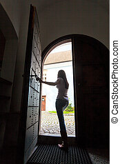 Woman walks out a door - Young Woman walks through an open...