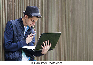 young man with computer outdoors