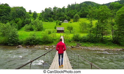 Man Walk Across a Suspension Bridge - A Young Man Tourist...