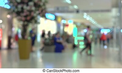 Unknown people walking in modern shopping mall. 4K bokeh...