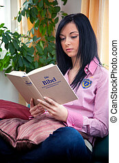 Religious young woman reading the Holy Bible