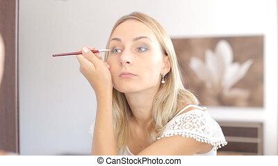 Beauty woman applying makeup. Beautiful girl looking in the mirror