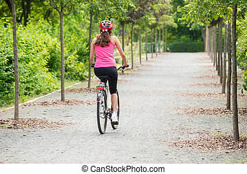 Female Cyclist Riding Away On Bicycle - Young Female Cyclist...
