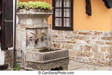 Fountain of old rural house - Old vintage stone fountain in...
