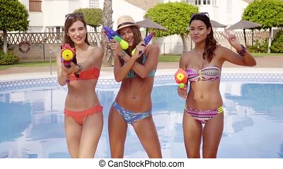 Three sexy girls with water guns - Three sexy bikini girls...
