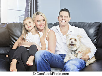 Family with pets sit on sofa at home