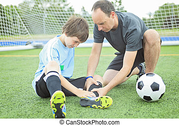 A young soccer player with ball on the field - A young...