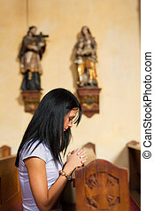 Women pray in a church - Young woman praying in a church