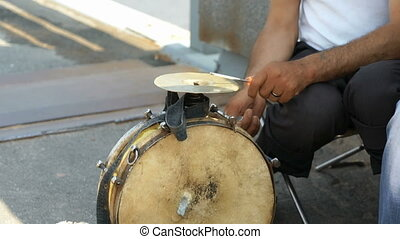 A tanned man playing on the old drum outdoors - A tanned man...