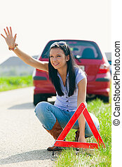 Woman with a warning triangle in case of breakdown - Young...