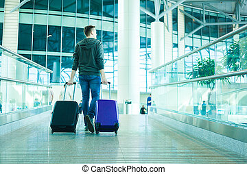 Young man with two cabin size bags in the airport - travel...
