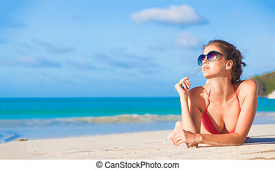 Young woman relaxing at the beach in the evening. Anse...