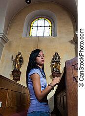 Women pray in a church - Young woman praying in a church