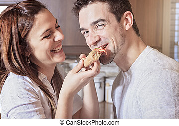 Happy young couple eating pizza at the kitchen - A Happy...