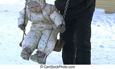 Baby girl sitting on swing in winter.