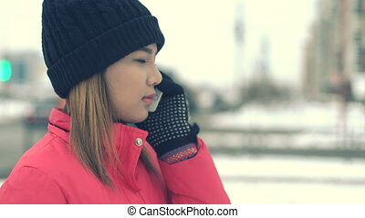 Woman talking on smart phone in winter city Toned video