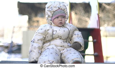 Baby girl sitting on a bench in winter.
