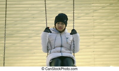 Young woman on swing in winter.