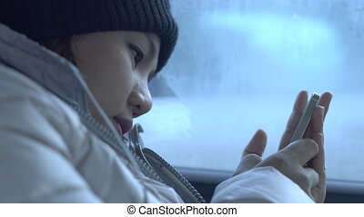 Girl playing with smartphone in transport.