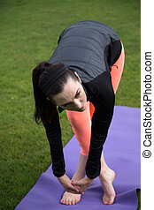 Athletic Woman Doing Yoga Outdoors - Photo of a very...