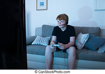 Boy Engrossed In Playing Videogames - Boy With Joystick...