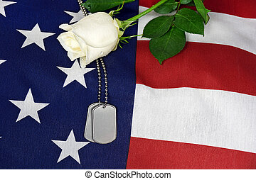 dog tags and rose on flag - Military dog tags and white rose...