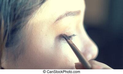 Young Lady using eye shadow. Closeup shot,