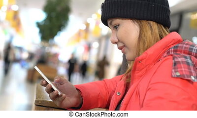 Young asian Woman using a smart phone in mall