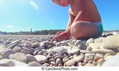 Small boy plays with stones on the natural pebble beach