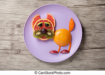 Funny cat made of grapefruit and orange on desk and plate