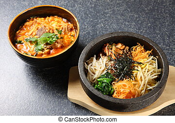 bibimbap and Korean hot soup on a dinibg table