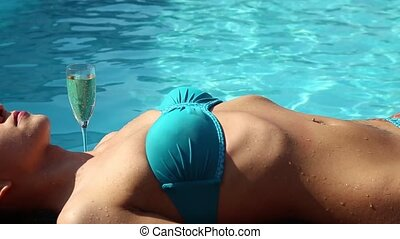 Woman has a rest in the pool with champagne.