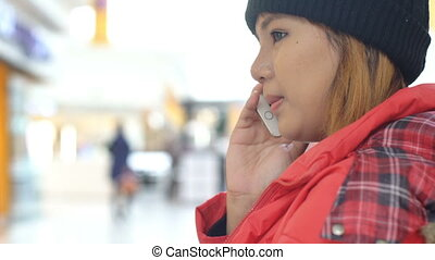 Young asian Woman talking on cell phone in mall