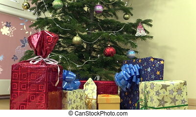 colorful gift present boxes with ribbon under christmas tree...