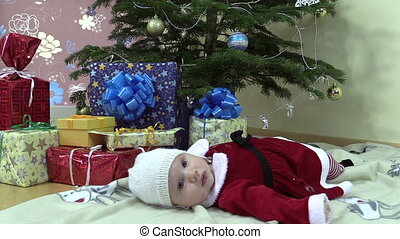 Cute baby girl lie near christmas tree and gift present boxes