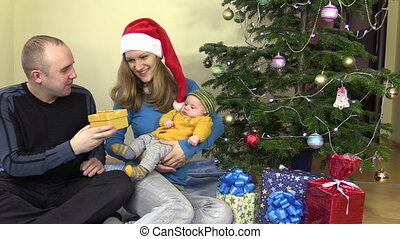 Cheerful family man and woman present gift for baby in Christmas
